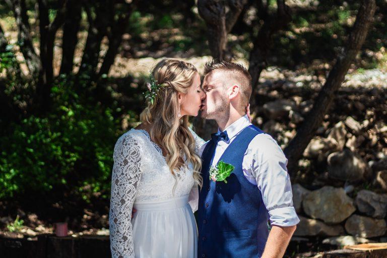Couple de mariés s'embrassant sous des pins